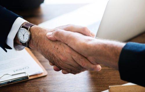 Service im digitalen Zeitalter: Handschlag zweier Geschäftsmänner