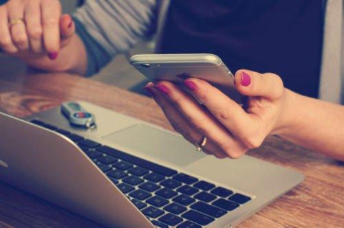 Service im digitalen Zeitalter: Frau mit Smartphone in der Hand sitzt vor einem Laptop